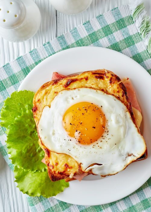 hot french toasts croque madame with slices of boiled ham, melted emmental cheese and fried sunny side up egg served on a white plate with fork and knife on a table, view from above
